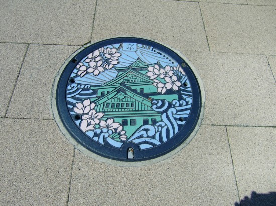 Blossoms-and-Building-on-Japanese-Manhole-Cover-by-Akibubblet-550x412.jpg