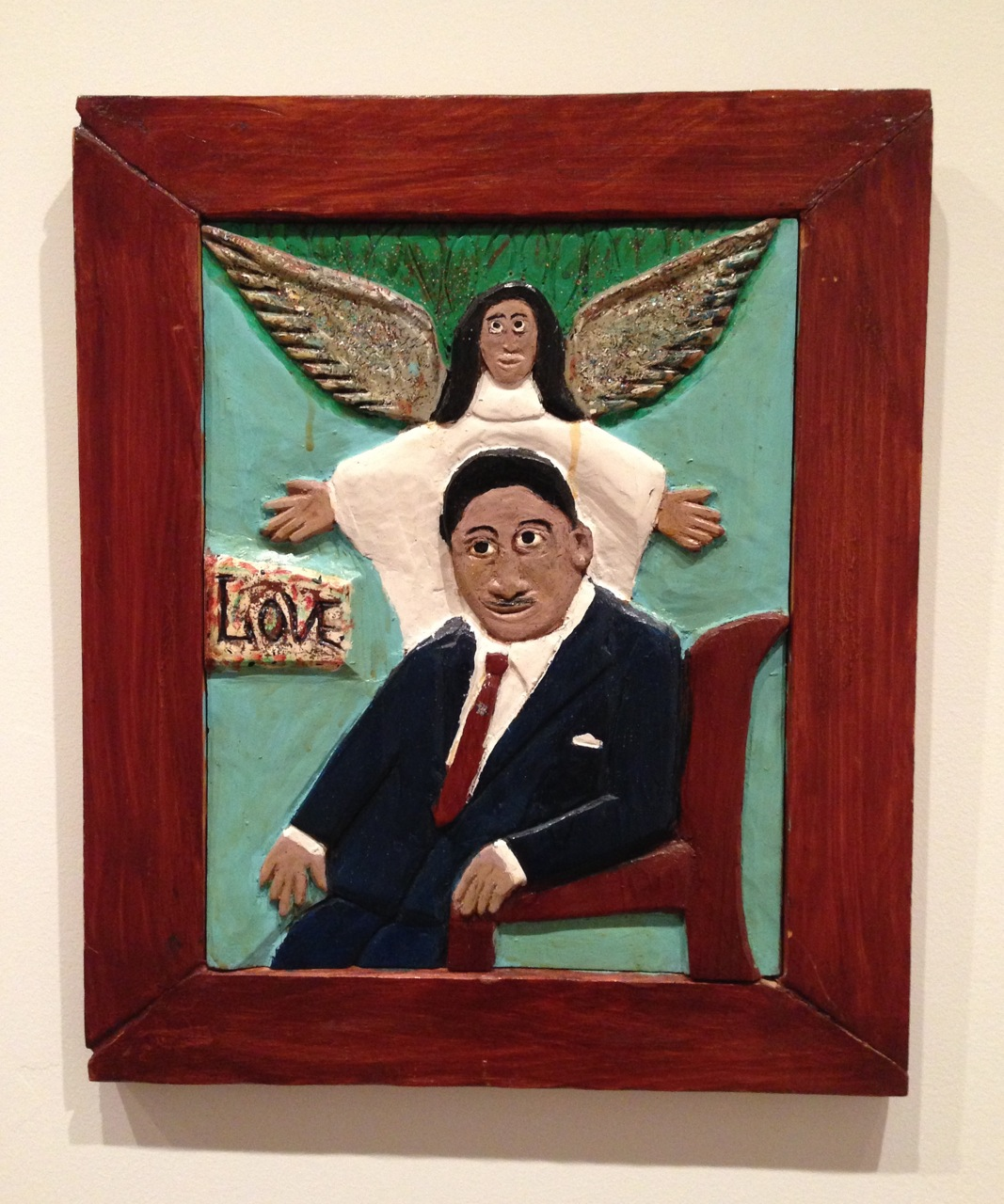 "Elijah Pierce, ""Love"" (Martin Luther King, Jr.). Paint, glitter, and local applications of varnish on carved wood; artist-made frame, 19 x 16  inches. (Photo by Michelle Aldredge from The Jill and Sheldon Bonovitz Collection from the Philadelphia Museum of Art)."