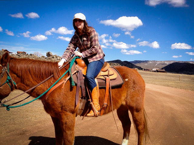 Michelle riding a horse during her residency at Brush Creek Ranch in Wyoming. The hat was on loan from Sunday Poet Kate Kingston! (Photo by Eun Young Lee)