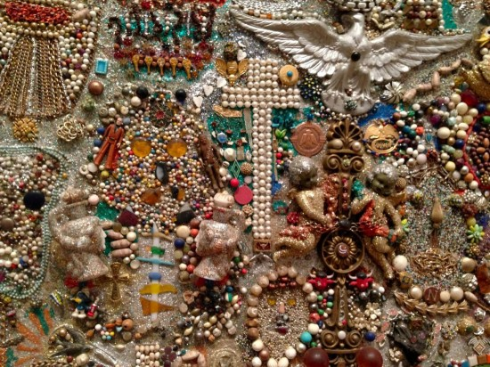 Simon Sparrow, Assemblage with Painted Frame. Glitter, paint, molded plastic figurines, boxes, watches, metal and plastic jewelry, buttons, shells, wooden beads, mirror, rocks, ceramic, and other found objects on wood; artist-made painted wood frame, 48 x 49 x 2 inches with frame. (Photo by Will Brown courtesy the Philadelphia Museum of Art, The Jill and Sheldon Bonovitz Collection)