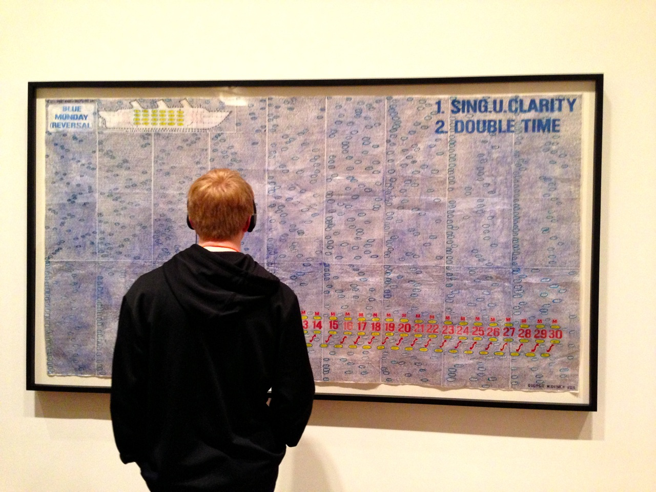 A museum visitor studies George Widener's Blue Monday Reversal, which is comprised of ?? dates in ballpoint pen and ink. (Photo by Michelle Aldredge from ??)