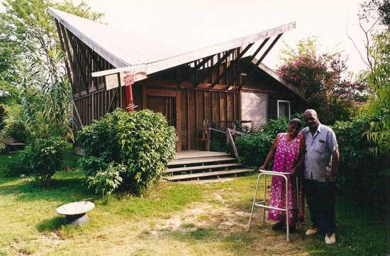 Anderson and Ora Lee Harris in front of the Butterfly House. The angled-roof supplies a means to collect and reuse rainwater in daily cleaning routines and an effective gray water plumbing system within the home. Samuel Mockbee encouraged the students building the Harrises' house to emphasize the porch area when he realized the amount of time the Harris family spent on their previous porch. The Butterfly House allowed the Harris family to live comfortably in an exaggerated version of their previous home. Rural Studio students provided Mrs. Harris, who is handicapped and navigates with a wheelchair, complete mobility within her home by constructing subtle access ramps, wide doorways and low bathroom features. The walls of the home were formed using salvaged wood from a recently razed 105 year-old church near the site. (Photo courtesy Dean, Andrea Oppenheimer. Rural Studio: Samuel Mockbee and an Architecture of Decency, Princeton Architectural Press, 2002)