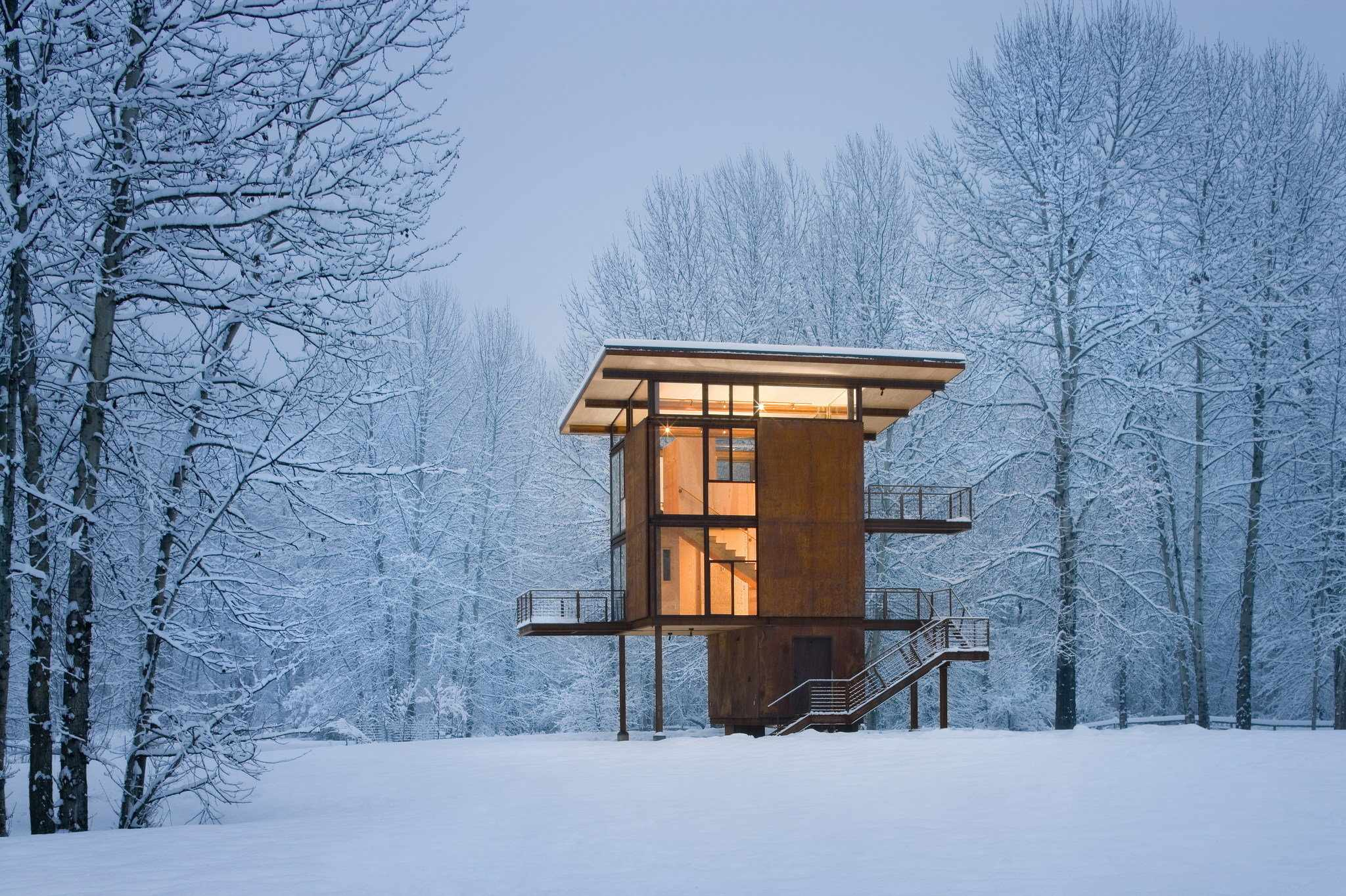This 1,000 square-foot weekend cabin designed by architect Tom Kundig is basically a steel box on stilts and can be completely shuttered when the owner is away. Situated near a river in a floodplain, the 20' x 20' square footprint rises three stories and is topped by the living room/kitchen. Large, 10' x 18' steel shutters can be closed simultaneously using a hand crank. (Photo by Tim Bies courtesy Olson Kundig Architects)