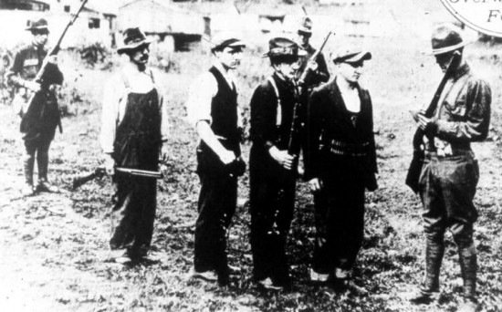 Miners turn their weapons over to soldiers after the strike at Blair Mountain ends