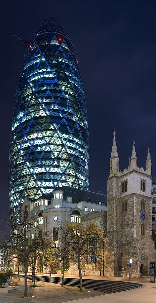 Night view of 30 St Mary Axe (commonly known as the Gherkin) and St Andrew Undershaft in London (Photo via Wikipedia)